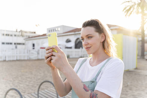 Young woman spending a day at the seaside, taking selfie - AFVF05399