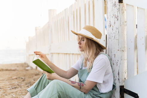 Young woman spending a day at the seaside, reading a book on the beach - AFVF05402