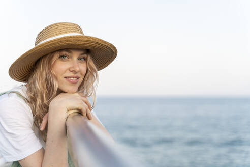 Young woman spending a day at the seaside, leaning on railing, portrait - AFVF05408