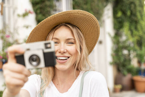 Portrait of happy young woman with camera - AFVF05420
