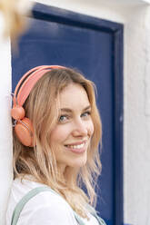 Portrait of happy young woman  leaning at facade listening music with headphones - AFVF05423