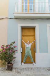 Young woman standing at house entrance - AFVF05426