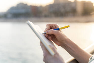Crop view of young woman writing in notebook at evening twilight - AFVF05429