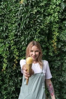 Portrait of smiling young woman offering ice cream cone - AFVF05431