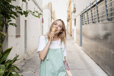 Portrait of tattooed young woman with ice cream cone in the city - AFVF05434