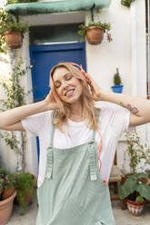 Portrait of young blond woman with eyes closed listening music with headphones - AFVF05443