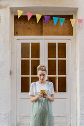Portrait of young woman with smartphone standing in front of wooden door - AFVF05449