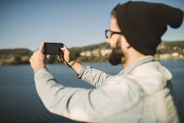 Young man taking smartphone selfies by the sea - RAEF02340
