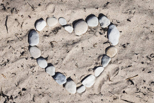 Heart made out of stones on sand - JOHF08055