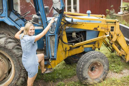 Woman entering tractor - JOHF08187