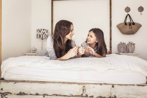 Mother and daughter lying on bed talking together - SDAHF00212