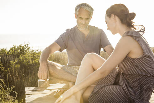 Couple sitting on boardwalk at the coast playing backgammon - SDAHF00263