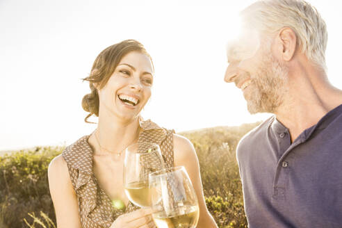 Happy couple having a glass of white wine at sunset - SDAHF00269
