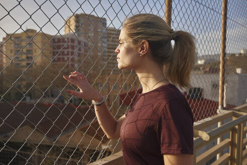 Sporty young woman looking through a fence - PACF00196