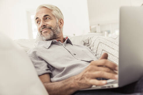 Mature man using laptop on couch at home - SDAHF00329