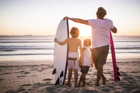 Rear view of father and sons with surfboards standing on the beach at sunset - SDAHF00432