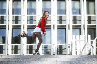 Blond woman balancing with roller skates - KIJF02893