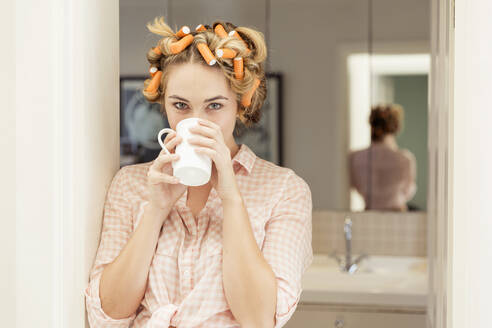 Portrait of young woman with curlers in hair drinking coffee - SDAHF00435