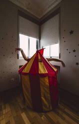 Person hiding behind toy tent in empty room - RAEF02352