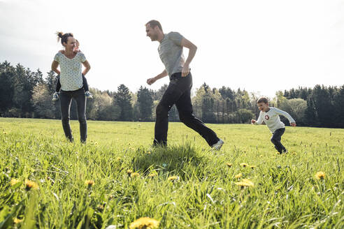 Family with two kids having fun together on a meadow in spring - WFF00271