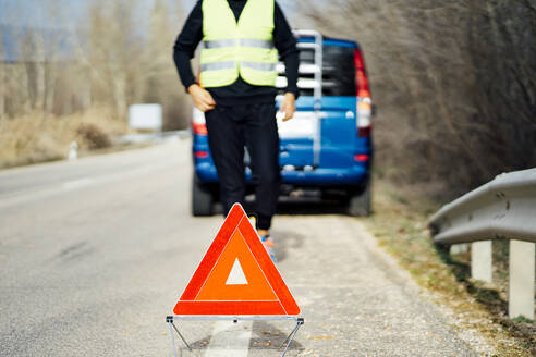 Man putting warning triangle on country road by van breakdown - CJMF00255