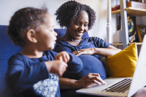 Happy pregnant woman with daughter using laptop on sofa - HOXF04956