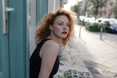 Portrait of red-haired woman in front of a cafe and looking sideways - OGF00123