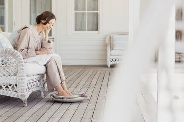 Woman having a footbath on a veranda - SDAHF00524