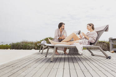 Couple relaxing on terrace at the poolside - SDAHF00536