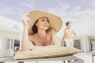 Woman relaxing on sun lounger with man in background - SDAHF00542