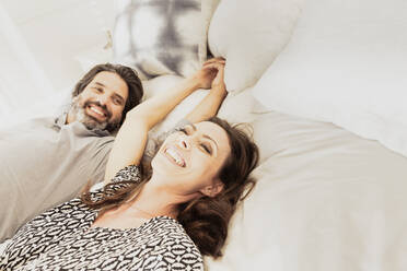 Happy couple lying in bed holding hands - SDAHF00548