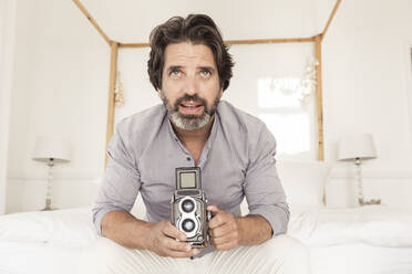Bearded man sitting on bed with old-fashioned camera - SDAHF00560