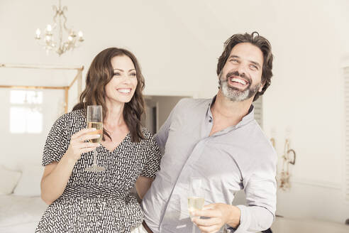 Happy couple drinking champagne in vacation home - SDAHF00566