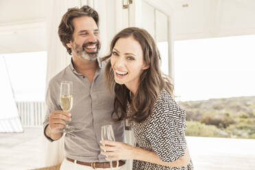 Happy couple drinking champagne in vacation home - SDAHF00569