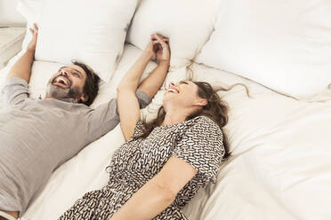 Laughing couple lying in bed holding hands - SDAHF00572