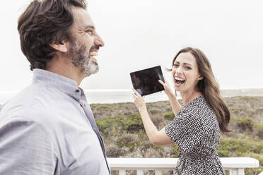 Happy man with woman holding tablet at the coast - SDAHF00575