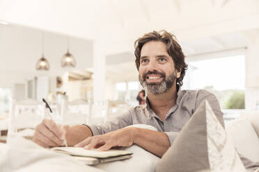 Smiling bearded man sitting on couch taking notes - SDAHF00581