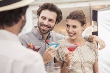 Couple and friend socializing on a cocktail party - SDAHF00587