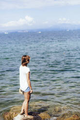 Young woman standing at the lakeside, Lake Garda, Italy - GIOF08002