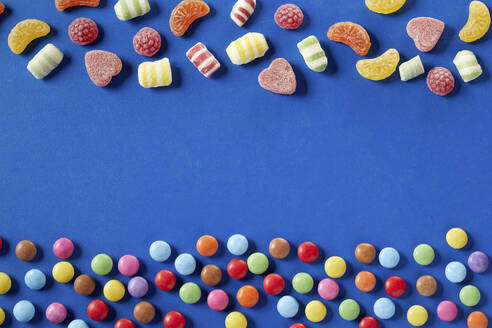 Colorful candies on bue background, copy space - DREF00052
