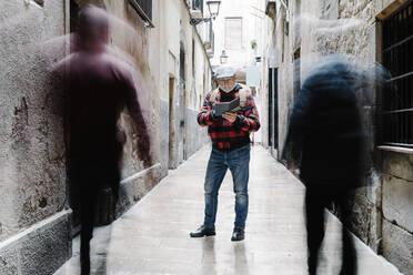 Senior man using guidebook in the city, Barcelona, Spain - JCZF00012