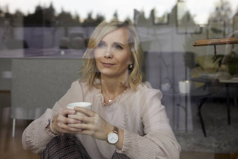 Portrait of blond woman behind windowpane at home - RBF07056