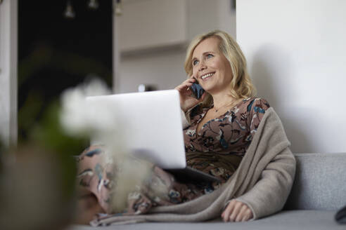 Blond woman with smartphone and laptop on couch at home - RBF07059