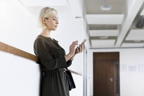 Portrait of businesswoman leaning against wall using mobile phone - BMOF00178