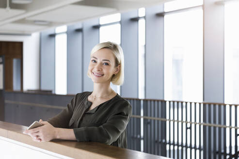 Portrait of happy businesswoman with mobile phone leaning on railing - BMOF00181