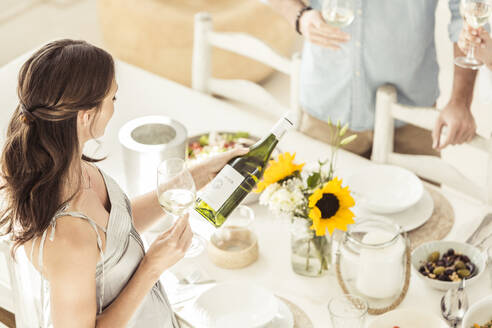 Woman holding wine bottle during lunch - SDAHF00635