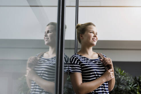 Portrait of a smiling young woman in office reflected in glass pane - BMOF00186
