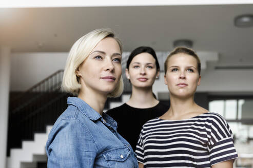 Portrait of confident young businesswomen in office looking away - BMOF00192