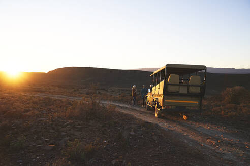 Safari off-road vehicle and tourists at sunset roadside South Africa - CAIF23758
