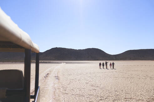 Safari tour guide and group sunny arid wildlife reserve South Africa - CAIF23785